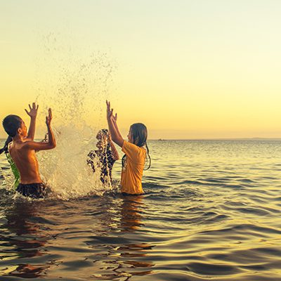 Live Well - Kids playing in the water at sunset
